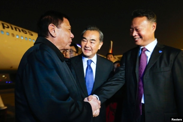 President of the Philippines Rodrigo Duterte (L) shakes hands with Chinese ambassador to the Philippines Zhao Jianhua (R), as Chinese Foreign Minister Wang Yi (C) looks on, at airport in Beijing, Oct. 18, 2016.
