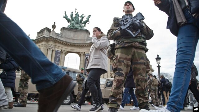 A French legionnaire patrols outside the Grand Palais museum near the Champs Elysees avenue in Paris, part of the reinforced security guarding gathering places around France, Dec. 30, 2015.