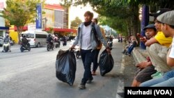 Relawan kebersihan memastikan lokasi aksi bersih kembali. (Foto:VOA/ Nurhadi)