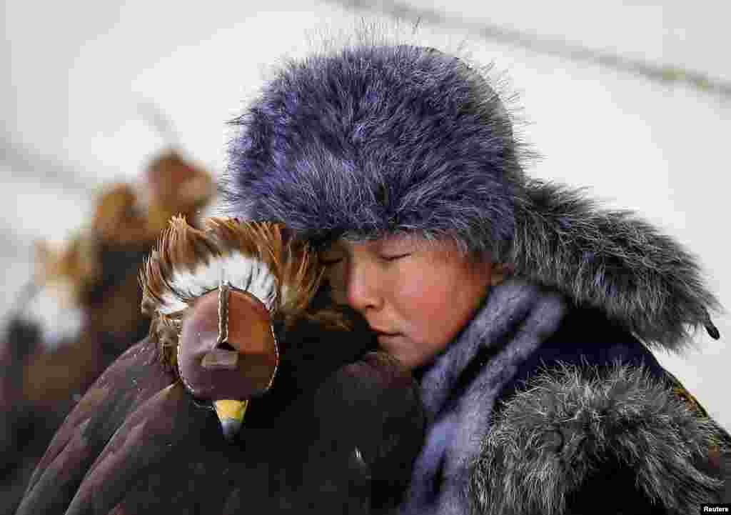 A young hunter rests next to his tamed golden eagle during an annual hunters competition at Almaty hippodrome, Kazakhstan February 9, 2018.