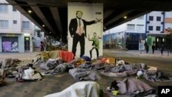 Para tunawisma tidur di bawah jembatan di depan mural yang menggambarkan Presiden A. Donald Trump sebagai dalang yang memanipulasi Presiden Brasil Jair Bolsonaro, di pusat kota Sao Paulo, Brasil, 23 Juli 2019. (Foto: AP)