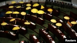 Pro-democracy lawmakers open yellow umbrellas, symbol of the Occupy Central movement, during a Legislative Council meeting as a gesture to boycott the government in Hong Kong, January 7, 2015.