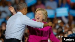 FILE - President Barack Obama and Democratic presidential candidate Hillary Clinton embrace during a campaign rally in Charlotte, North Carolina, July 5, 2016.
