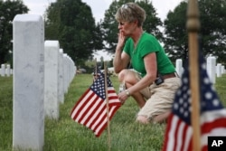 Anita Dixon, of Wichita, Kan., whose son Army Sgt. Evan Parker was killed while serving in Iraq in 2005, kisses the graves in section 60, where many of the casualties from Iraq and Afghanistan are buried, among flags placed in preparation of Memorial Day at Arlington National Cemetery in Arlington, Virginia, on Thursday May 27, 2010.