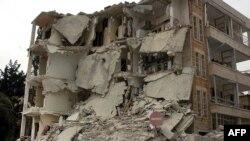 در اين عکس که توسط خبرگزاری رسمی سوريه (سانا) منتشر شد، يک مرد سوری (ايستاده در سمت چپ) در مقابل ساختمانی که روز دوشنبه، ۱۱ ارديبهشت ۱۳۹۱، بر اثر انفجار بمب خراب شد ايستاده است.