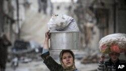 شام میں لڑائی سے متاثرہ ایک علاقے سے مقامی خاتون اور لڑکی نقل مکانی کر رہی ہیں