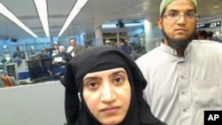 FILE - Tashfeen Malik, left, and Syed Farook pass through O'Hare International Airport in Chicago, July 27, 2014. Farook's iPhone is at the center of a standoff between Apple and the FBI.