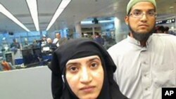 This July 27, 2014, photo provided by U.S. Customs and Border Protection shows Tashfeen Malik, left, and Syed Farook, as they passed through O'Hare Airport in Chicago. U.S. law enforcement is trying to gain access to information contained in Farook's iPhone.