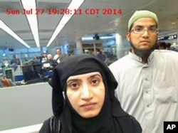 This July 27, 2014 photo provided by U.S. Customs and Border Protection shows Tashfeen Malik, left, and Syed Farook, as they passed through O'Hare International Airport in Chicago.