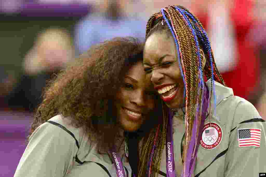 US Serena Williams (L) and Venus Williams celebrate on the podium after receiving their gold medal for winning the London 2012 Olympic Games women's doubles tennis tournament, August 5, 2012.