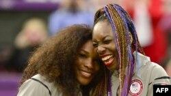 Petenis Serena Williams (kiri) dan kakaknya Venus Williams setelah meraih medali emas nomor ganda putri dalam Olimpiade 2012.