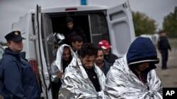 人们被警车送到克罗地亚的移民和难民中心