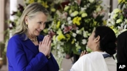 West Bengal Chief Minister Mamata Banerjee, right, and U.S. Secretary of State Hillary Rodham Clinton greet each other before a meeting in Kolkata, India, Monday, May 7, 2012. Clinton met with Banerjee, a key partner of India's ruling coalition who has st