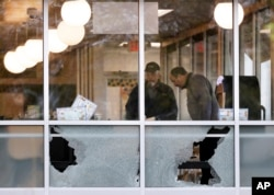 People look over the area near a window shot out at a Waffle House restaurant, April 22, 2018, in Nashville, Tenn. At least four people died after a gunman opened fire at the restaurant early Sunday.