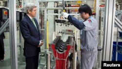 U.S. Secretary of State John Kerry (L) looks on as an engine is built during a tour of the Foton Cummins Engine plant in Beijing February 15, 2014. Kerry toured the plant and made remarks on climate change cooperation between the United States and China.