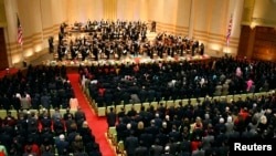 The U.S. and North Korean flags hang at the side of the stage and the audience stands while Music Director Lorin Maazel conducts the New York Philharmonic playing the U.S. national anthem before the start of their concert at the Grand Theatre in the Pyongyang, North Korea, Feb. 26, 2008.