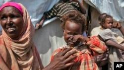 Người mẹ và con ngồi bên ngoài căn lều tạm bợ của họ trong trại tị nạn dành cho những người bị di dời vào năm 2012 bởi nạn đói hoặc chiến tranh ở Mogadishu, Somalia.