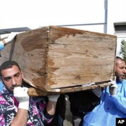 Men carry a coffin at Al-Jalaa hospital in Benghazi on Feb 2011