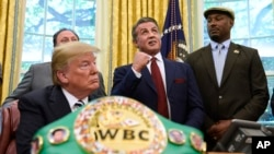 President Donald Trump (L), and heavyweight champion boxer, Lennox Lewis (R) watch with Sylvester Stallone in the Oval Office of the White House in Washington, May 24, 2018, where Trump granted a posthumous pardon to Jack Johnson, boxing's first black heavyweight champion.