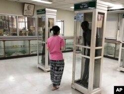 Seorang pengunjung mengamati jazad pembunuh berantai Si Ouey (kanan) yang diawetkan dan dipajang tegak dalam kotak kaca di Museum Rumah Sakit Siriraj Forensik, di Bangkok, Thailand, 17 Mei 2019.