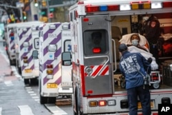 A patient arrives in an ambulance cared for by medical workers wearing personal protective equipment due to COVID-19 concerns outside NYU Langone Medical Center, April 13, 2020, in New York City.