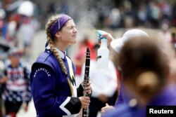 A member of the Waterville Junior/Senior High School marching band is sprayed with mist to prevent heatstroke while participating in a parade during Independence Day celebrations in Washington, July 4, 2019.