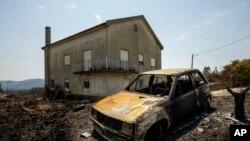 Sebuah mobil hangus terbakar akibat kebakaran hutan di dekat Roda, Portugal tengah, 23 Juli 2019. Layanan darurat di Portugal berhasil mengendalikan api besar yang mengamuk selama empat hari dan melukai 39 orang.