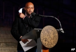 Denver Mayor Michael Hancock pulls off his mask to speak before red and white lights were illuminated on the City/County Building to show support and gratitude for first responders and medical personnel during the outbreak, April 9, 2020, in Denver.