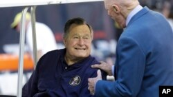 FILE - Former President George H.W. Bush talks with Houston Texans owner Bob McNair before a National Football League in Houston, Nov. 2014.