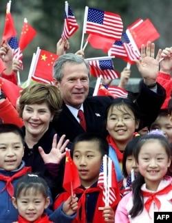 2002年2月22日亚洲之行最后一站: 美国总统乔治·W·布什(右)和第一夫人劳拉·布什(左)访问中国八达岭长城。