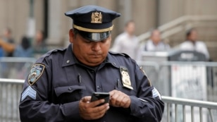 A New York City Police Department (NYPD) sergeant uses his mobile phone while on duty in lower Manhattan in New York City, US, May 25, 2016.
