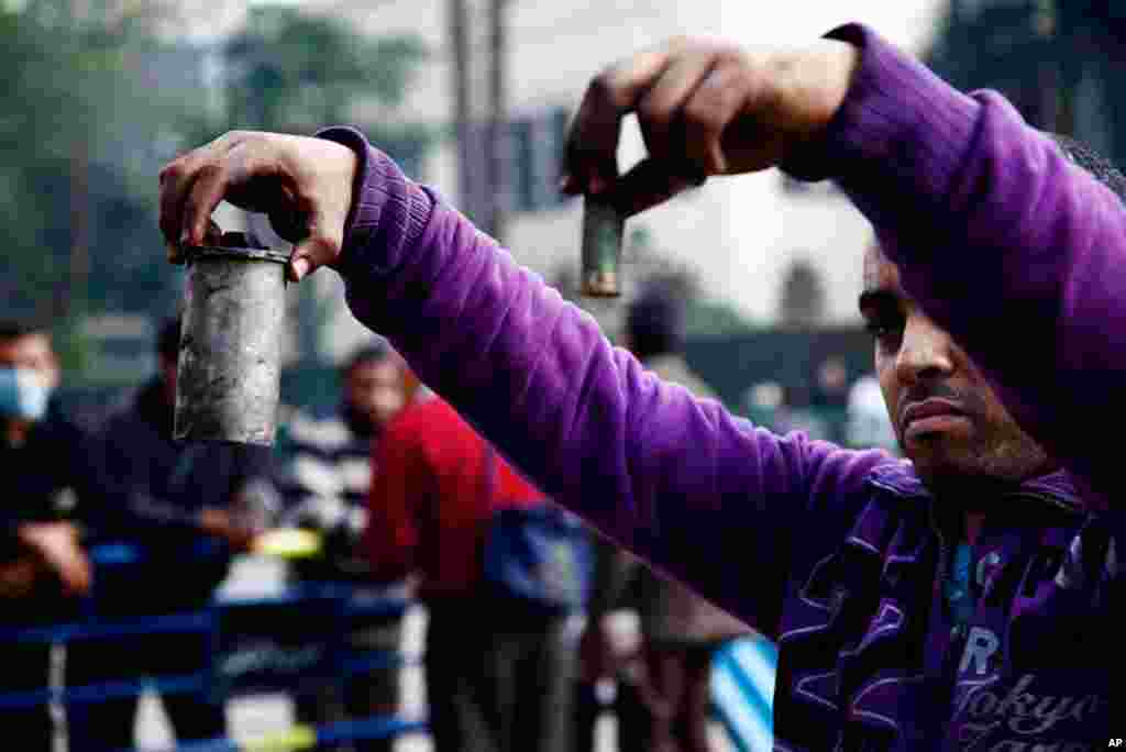 A protester on near Tahrir Square holds a spent shotgun shell and a tear gas canister. (VOA - Y. Weeks)