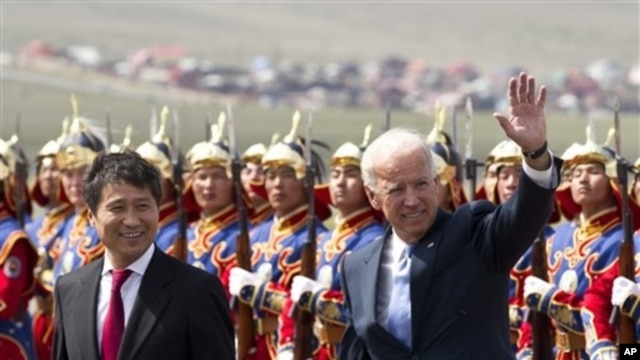 U.S. Vice President Joe Biden, right, waves as he walk with Mongolian Prime Minister Batbold Sukhbaatar  after they inspected honor of guards upon arrival at the Chinggis Khaan International Airport in Ulan Bator, Mongolia, August 22, 2011