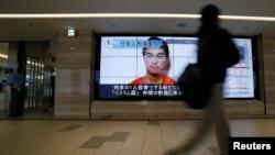 Seseorang di Tokyo berjalan melewati layar televisi yang menayangkan wajah sandera ISIS dari Jepang, Kenji Goto.