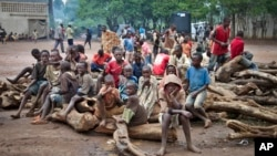 A group of Burundian refugee children sit on a pile of wood, at the Gashora refugee camp in the Bugesera district of Rwanda, April 21, 2015. Officials in Burundi say refugees in neighboring Rwanda are being recruited to fight against the Burundian government.