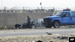People prepare to tow away a car damaged by a suicide car bomb explosion in the Iraqi town of Taji, north of Baghdad, Nov. 28, 2011