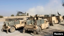 Helikopter NATO terbang di atas lokasi serangan pemberontak di markas gabungan NATO-Afghanistan di distrik Ghani Khel, provinsi Nangarhar (4/1). (Reuters/Parwiz)