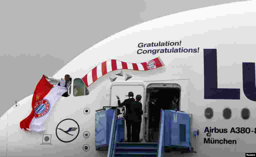 The pilot of an A380 aircraft carrying the Bayern Munich soccer players, waves a flag in team colors from a window of the plane on arrival at Munich airport, Germany, the day after Bayern Munich won the Champions League final soccer match at Wembley stadium in London.