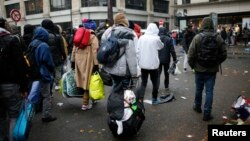 Migrants as they transfer to reception centers across the country during the dismantlement of makeshift camps, Stalingrad metro station, Paris, France, Nov. 4, 2016.