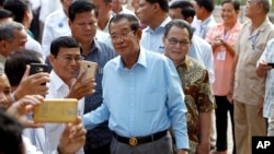 Cambodian Prime Minister Hun Sen, center, of ruling Cambodian People's Party pose for a selfie with his party supporters after a voting in the Senate election Sunday, Feb. 25, 2018. (AP Photo/Heng Sinith)