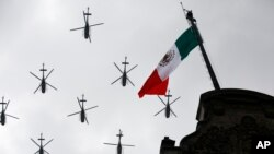 FILE - Military helicopters fly past the Mexican flag atop the National Palace, during the annual Independence Day military parade in Mexico City's main square, Sept. 16, 2016.