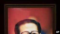 一位妇女走过江泽民画像.当局否认江已经去世.
