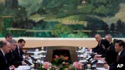 U.S. National Security Adviser Tom Donilon, left, and Chinese President Xi Jinping, right, attend their meeting at the Great Hall of the People in Beijing, May 27, 2013.