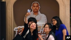 "FILE - a group of Chinese women take a selfie with a poster of Indian Bollywood blockbuster film ""Dangal"" on display at a cinema in Beijing."