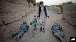 Một thường dân Afghanistan đi giữa các binh sĩ Hoa Kỳ tại 1 chốt kiểm tra trong thành phố Kandahar, Afghanistan, 21/10/2010
