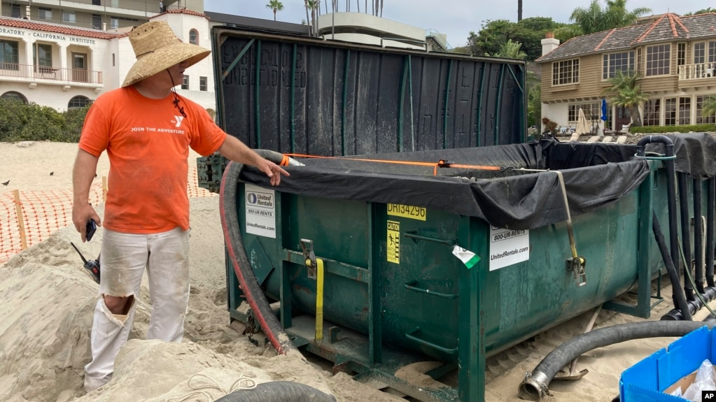 Marine scientist Robert Mooney shows a tank that some of an invasive algae was being pumped into from the harbor in Newport Beach, Calif., Wednesday, July 7, 2021.