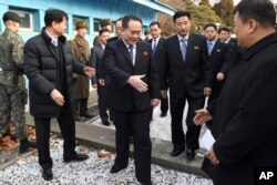 Head of North Korean delegation Ri Son Gwon, center, is greeted by South Korean officials after he crosses the border line to attend their meeting at Panmunjom in the Demilitarized Zone in Paju, South Korea, Jan. 9, 2018.