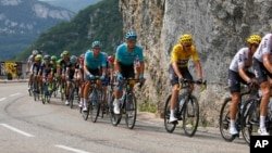 Britain's Chris Froome, wearing the overall leader's yellow jersey, rides in the pack with Denmark's Jakob Fuglsang, second left from Froome, during the eighth stage of the Tour de France cycling race more than 187.5 kilometers (116.5 miles) with start in Dole and finish in Station des Rousses, France, July 8, 2017.