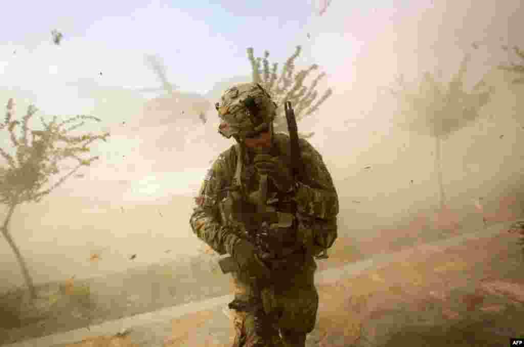15 tháng 9: Một quân nhân Mỹ tránh bụi mù trời do trực thăng Blackhawk bốc lên trong cuộc hành quân ở tỉnh Kunar của Afghanistan. (AP Photo/David Goldman)