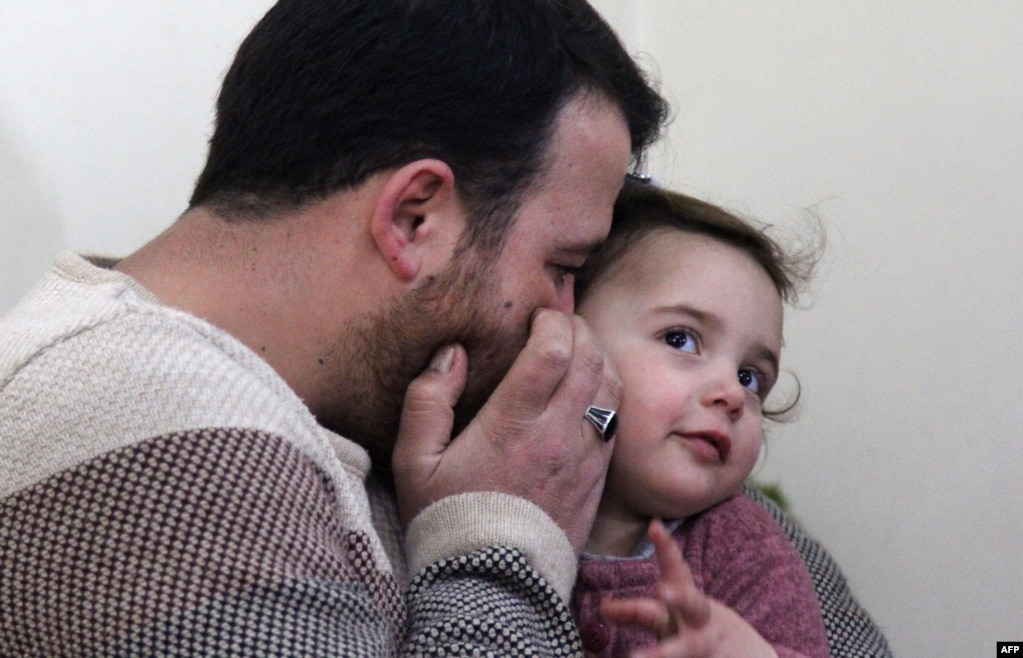 Syrian father Abdullah al-Mohammed speaks softly into the ear of his three-year-old daughter Salwa at their home in Sarmada.  The town is in Syria's last rebel pocket in the Idlib province, which Russian-backed Syrian regime forces are trying to crush.
